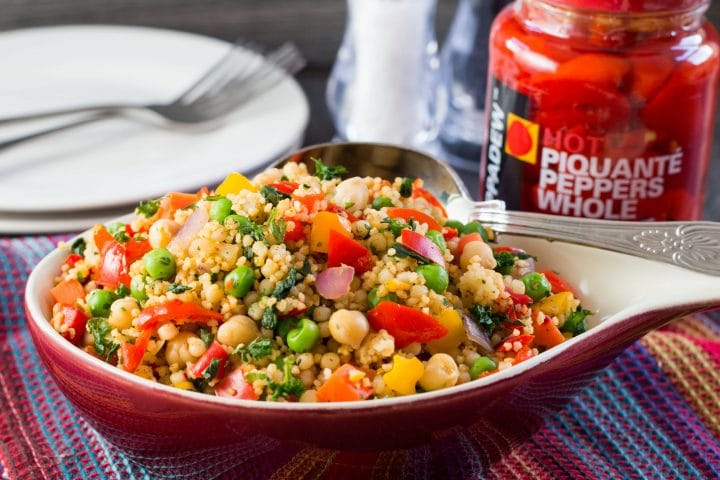 A red bowl filled with Moroccan Spiced Vegetable Couscous speckled with colourful mixed vegetables, chick peas, and different sized couscous.