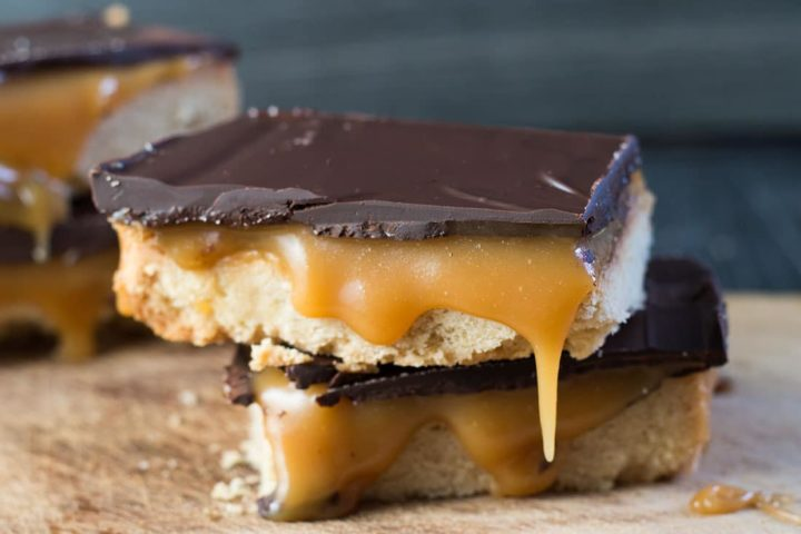 two slices of billionaire shortbread stacked with the caramel from the top slice oozing out to the cutting board below.