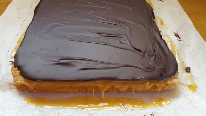 the Billionaire Shortbread removed from the pan showing each layer of shortbread, oozing caramel and the set chocolate.