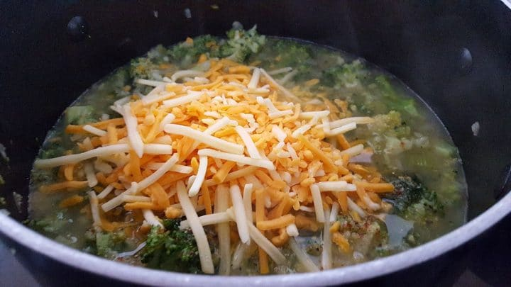 A pot with cooked broccoli florets in stock topped with a pile of shredded cheese to be stirred in.