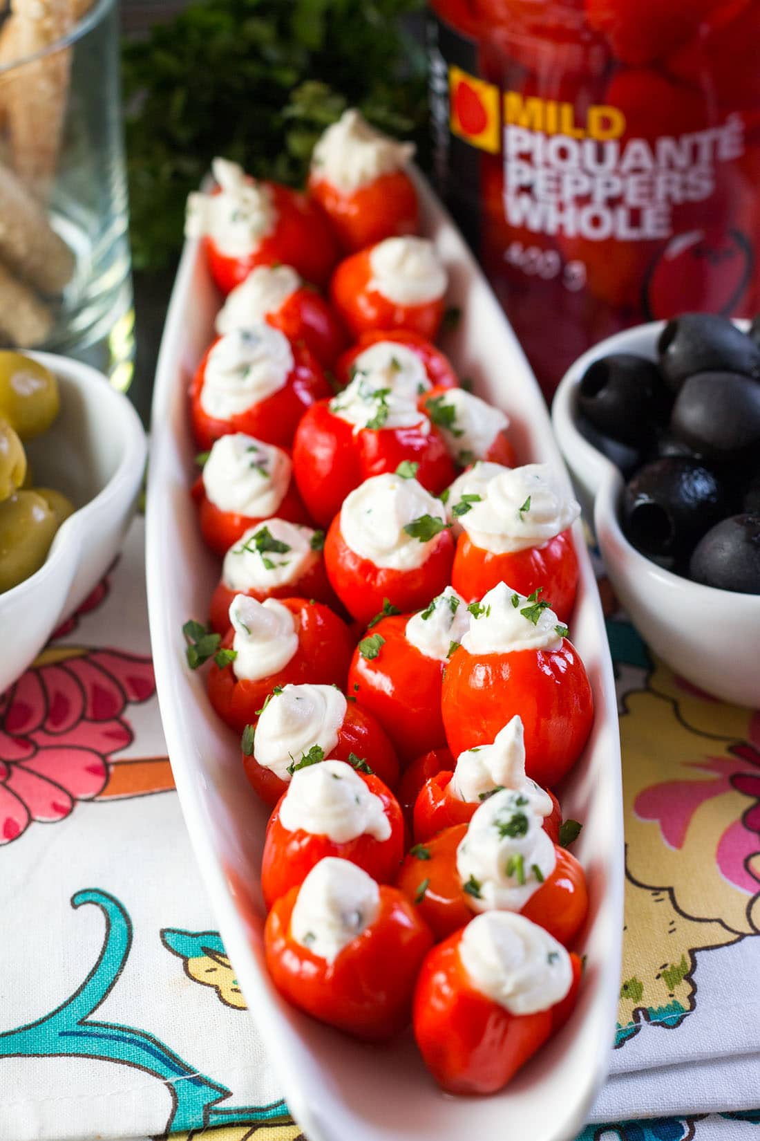 A plate of the stuffed peppers with bowls of olives on either side.