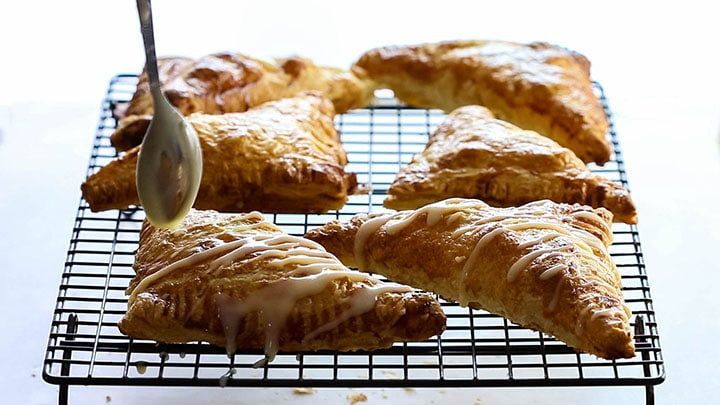 Apple turnovers on a cooling rack drizzled with icing.