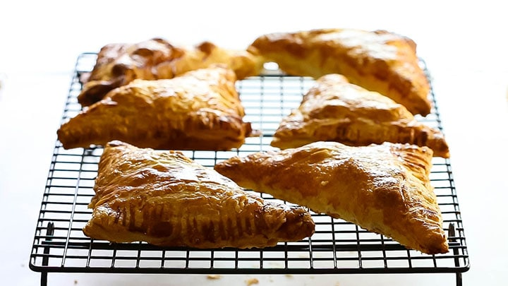 Apple Turnovers that are crisp and golden brown cooling on a wire rack.