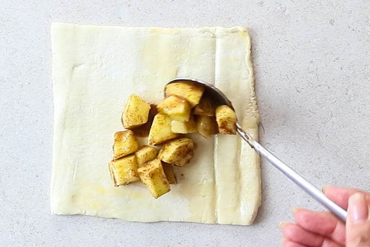 Apple mixture being spooned onto puff pastry dough