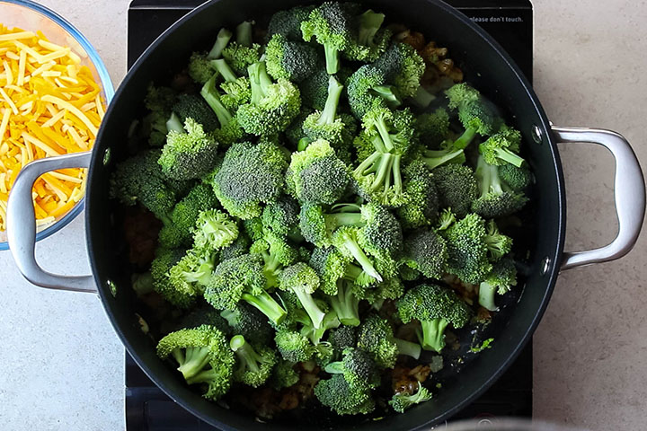 The broccoli added to the pan with the spices, onion, and garlic