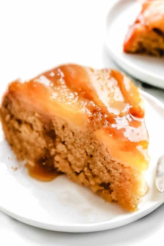 a slice of cake with baked apple on top