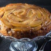 A close up of an apple cinnamon upside-down cake on a serving plate