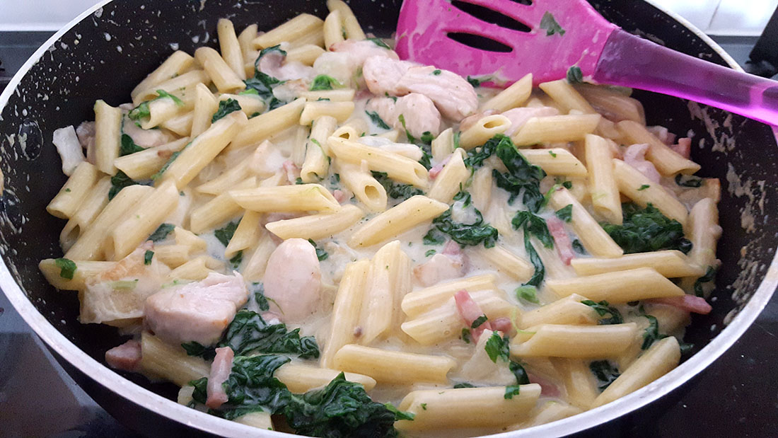 A pan with Creamy Chicken and Bacon Pasta cooking with a spatula mixing.