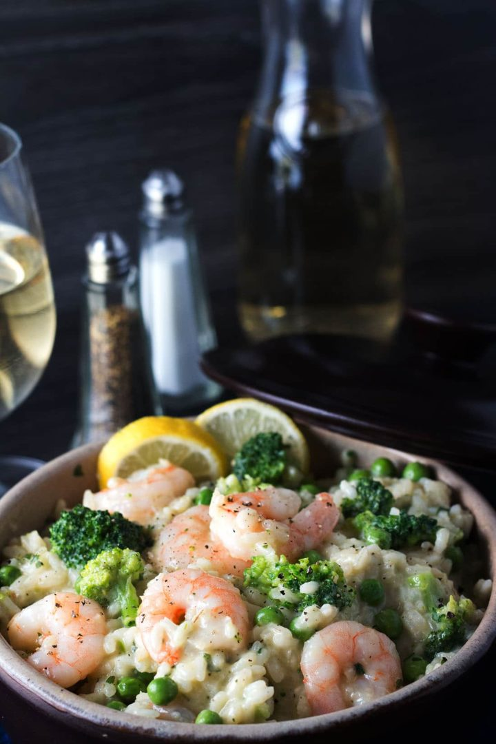 Easy Lemon Shrimp Risotto in a bowl with lemon wedges, a glass of white wine and salt and pepper mills in the background