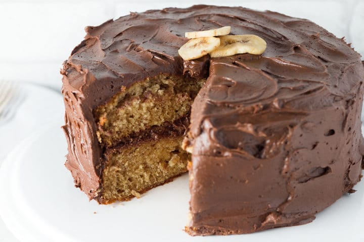 Banana Spice Cake with Chocolate Fudge Frosting with a piece taken out of it on a white background