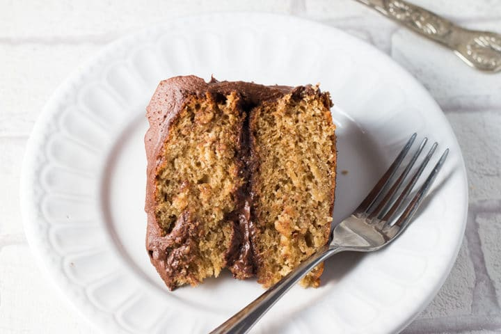 Banana Spice Cake with Chocolate Fudge Frosting on a plate with a fork beside