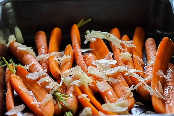Thin sliced garlic added to the carrots in the pan