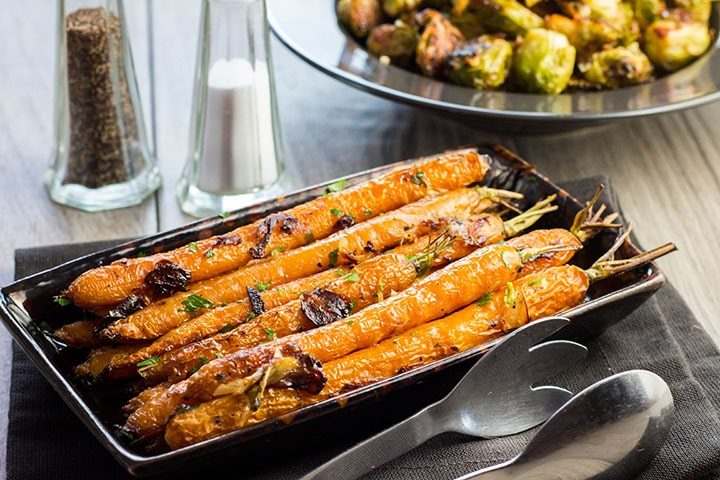Garlic Roasted Carrots on a serving dish sprinkled with parsley
