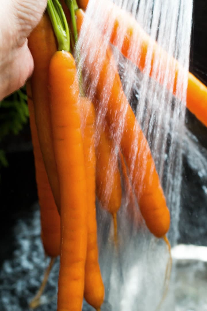 Fresh carrots being washed under running water.