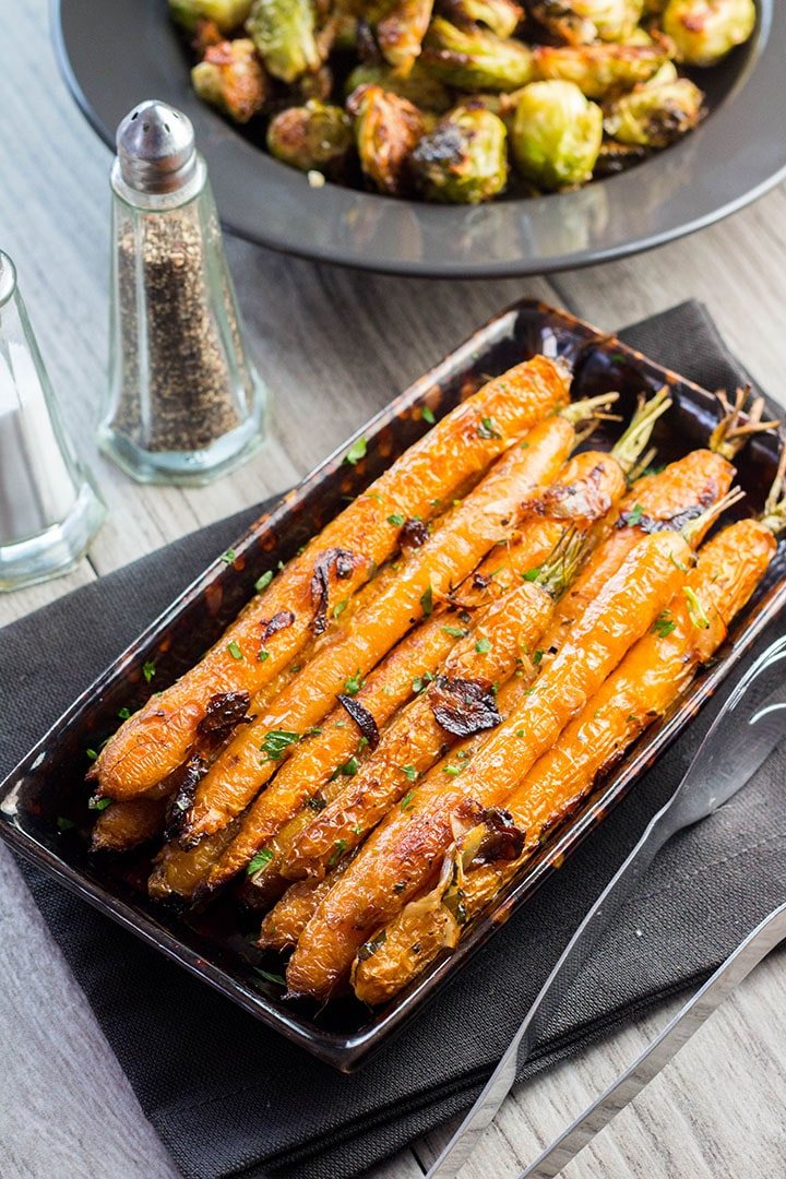 Buttery Balsamic Garlic Roasted Carrots on a serving dish sprinkled with parsley