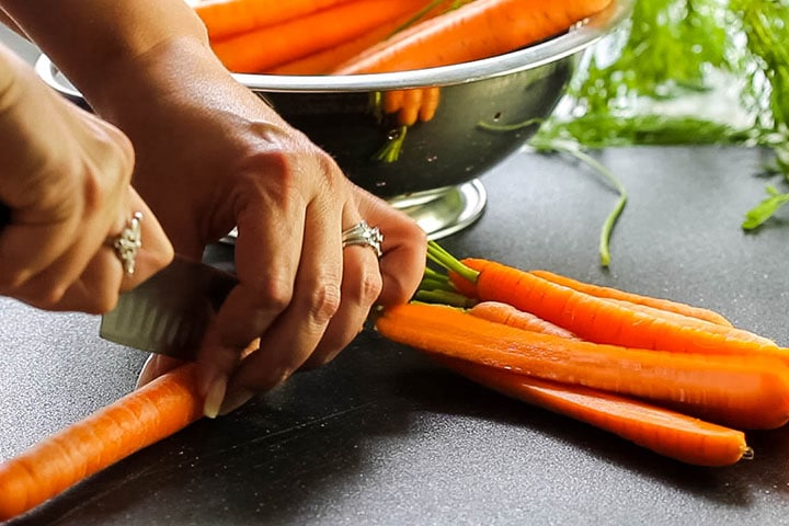 A carrot being cut in half lengthwise.