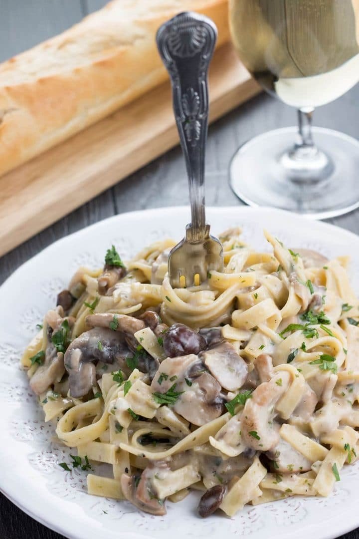 Creamy Tagliatelle and Mushrooms on a plate with a fork twirling the pasta.