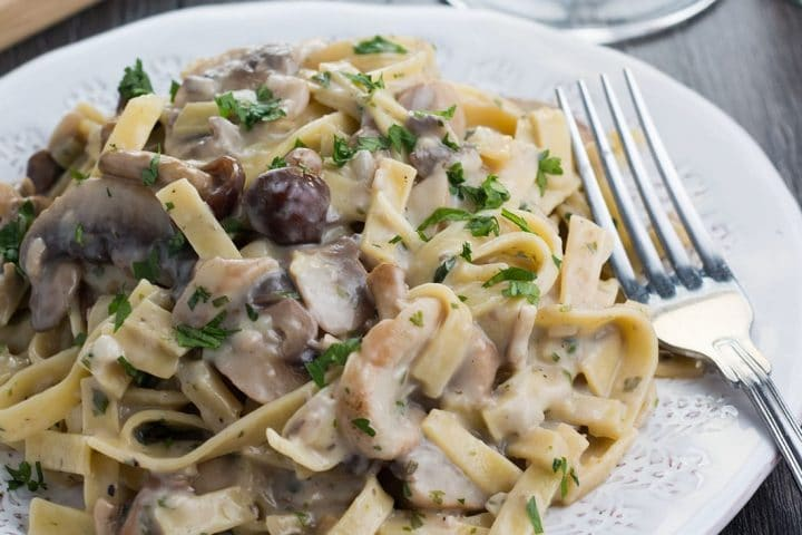 A plate of Creamy Tagliatelle and Mushrooms on a plate with a fork next to it.