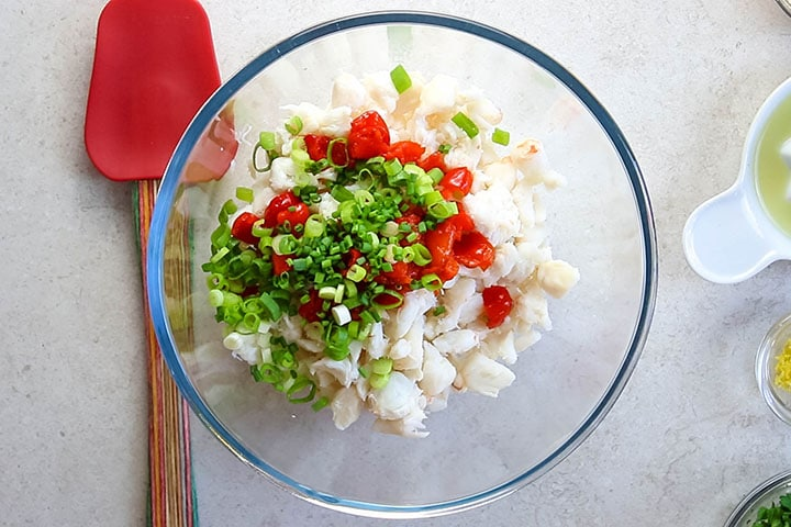 Chopped peppers, chives and green onions in the bowl with the crab