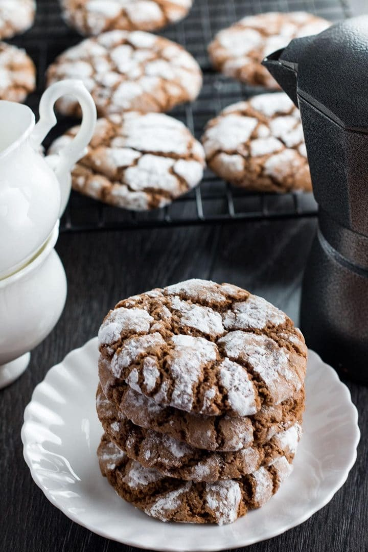 Three Spiced Ginger Crinkle Cookies on a plate with more on a cooling rack in the background