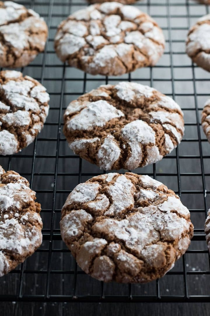 Cookies with a crackle effect covered in a sugar coating cooling on a wire rack