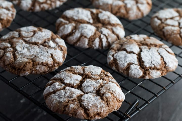 Spiced Ginger Crinkle Cookies fresh out of the oven cooling on a cooling rack.
