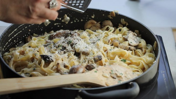 Tagliatelle in a pan covered in a creamy mushroom sauce with grated cheese and fresh cut parsley