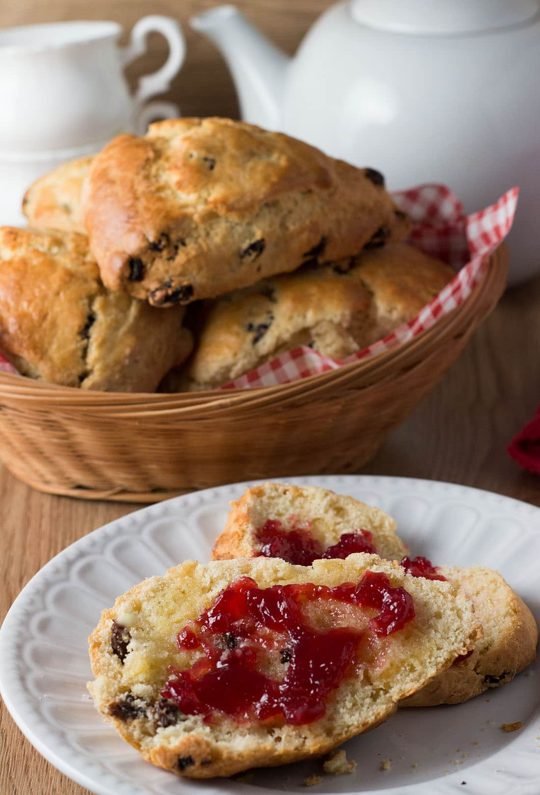 A raisin scone halved with butter and jam, with more raisin scones in the background.