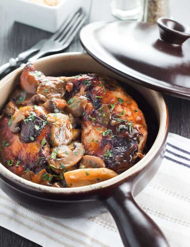 Coq Au Vin in a serving dish with the cover behind it