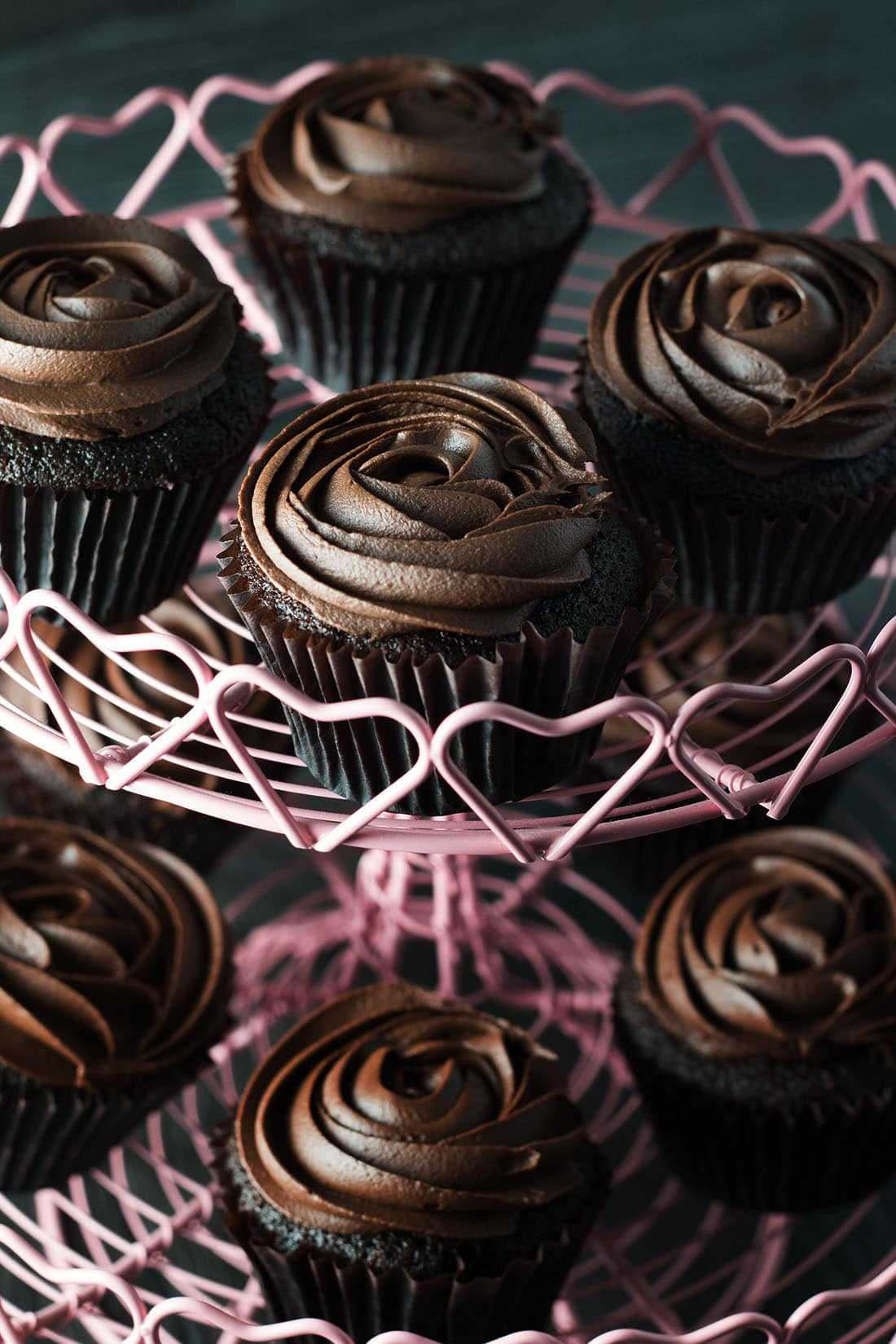 A selection of devils food cupcakes with chocolate icing in a rose swirl on a pink cupcake stand with heart design