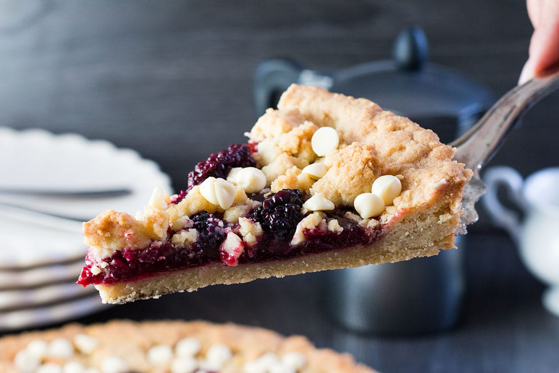 Raspberry and White Chocolate Shortbread Tart slice on cake slice being lifted from the freshly baked pie
