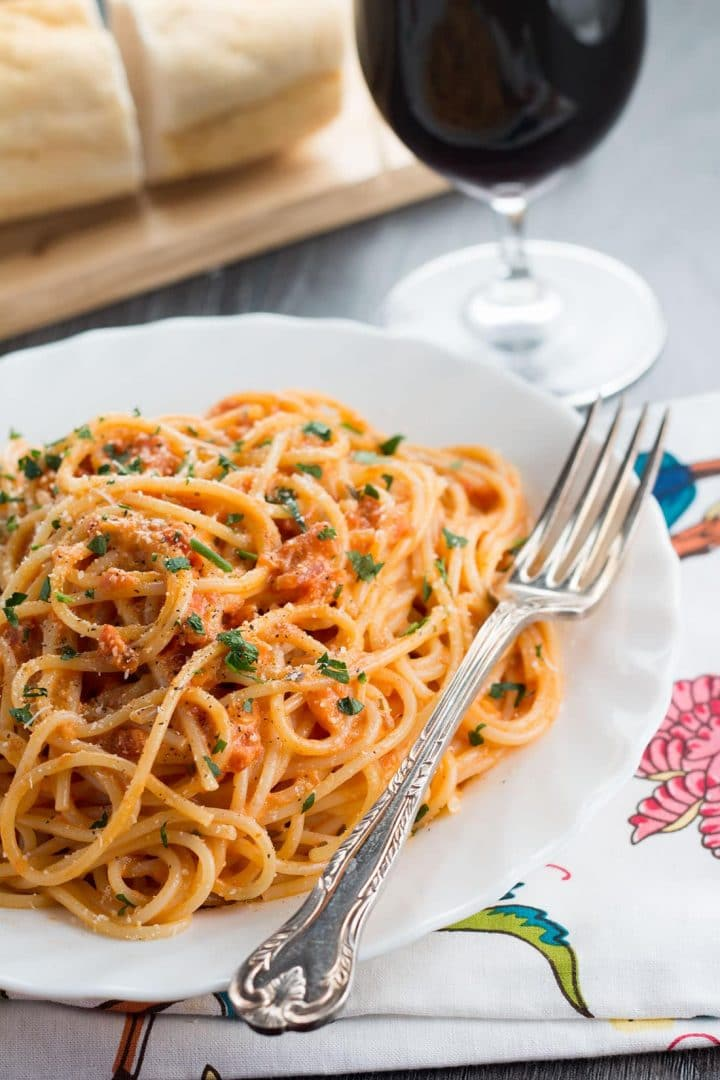 A plate white plate with the skinny spaghetti with tomato cream sauce that's sprinkled with grated cheese and parsley. A fork on the plate with a glass of red wine in the background