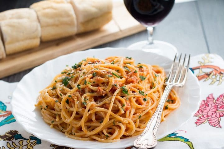 A plate of spaghetti with tomato cream sauce that's sprinkled with grated cheese and parsley.