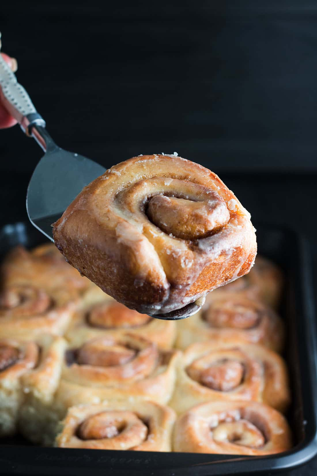 one vanilla bean cinnamon bun being served with the rest of the pan in the background.
