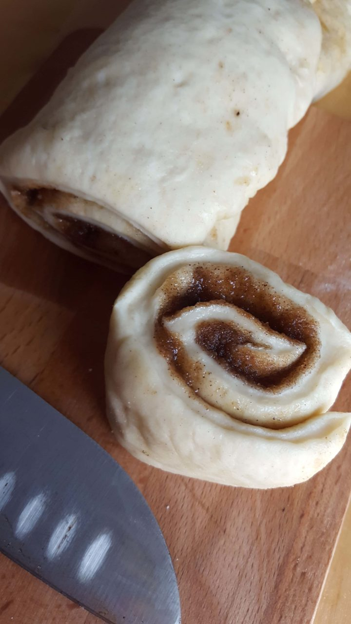 The rolled up dough on a cutting board with one bun cut showing the swirls of cinnamon and a knife next to it.