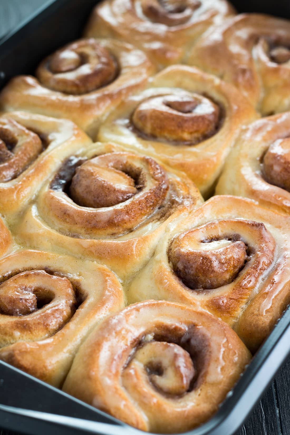 Freshly baked golden brown vanilla bean cinnamon buns in the pan covered with glistening glaze