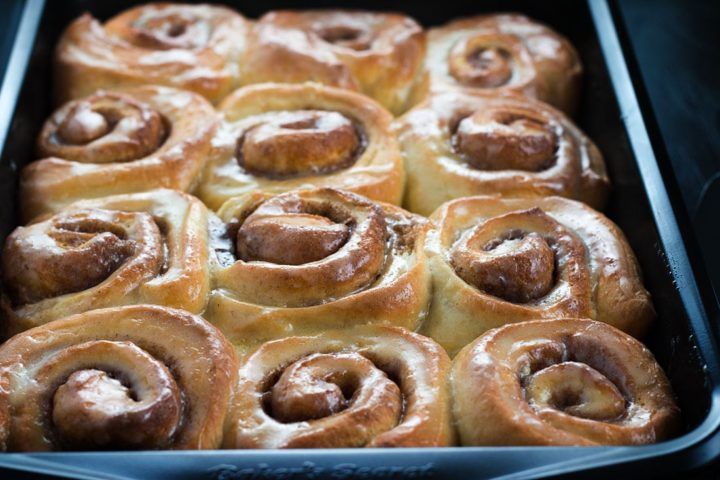 Fresh baked Vanilla Bean Cinnamon Buns in the pan shiny with glaze