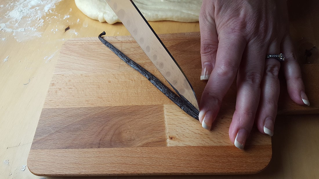 A vanilla pod being sliced down the middle with a knife,