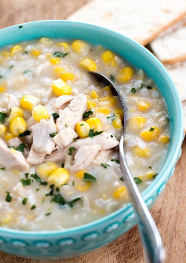 A bowl of chicken and rice corn chowder with a spoon in it
