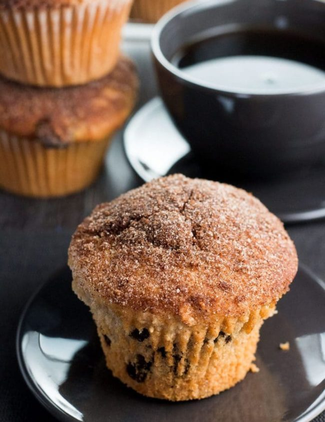 A Cinnamon Raisin Jumbo Muffin Topped with Cinnamon Sugar on a plate with a cup of coffee behind it.