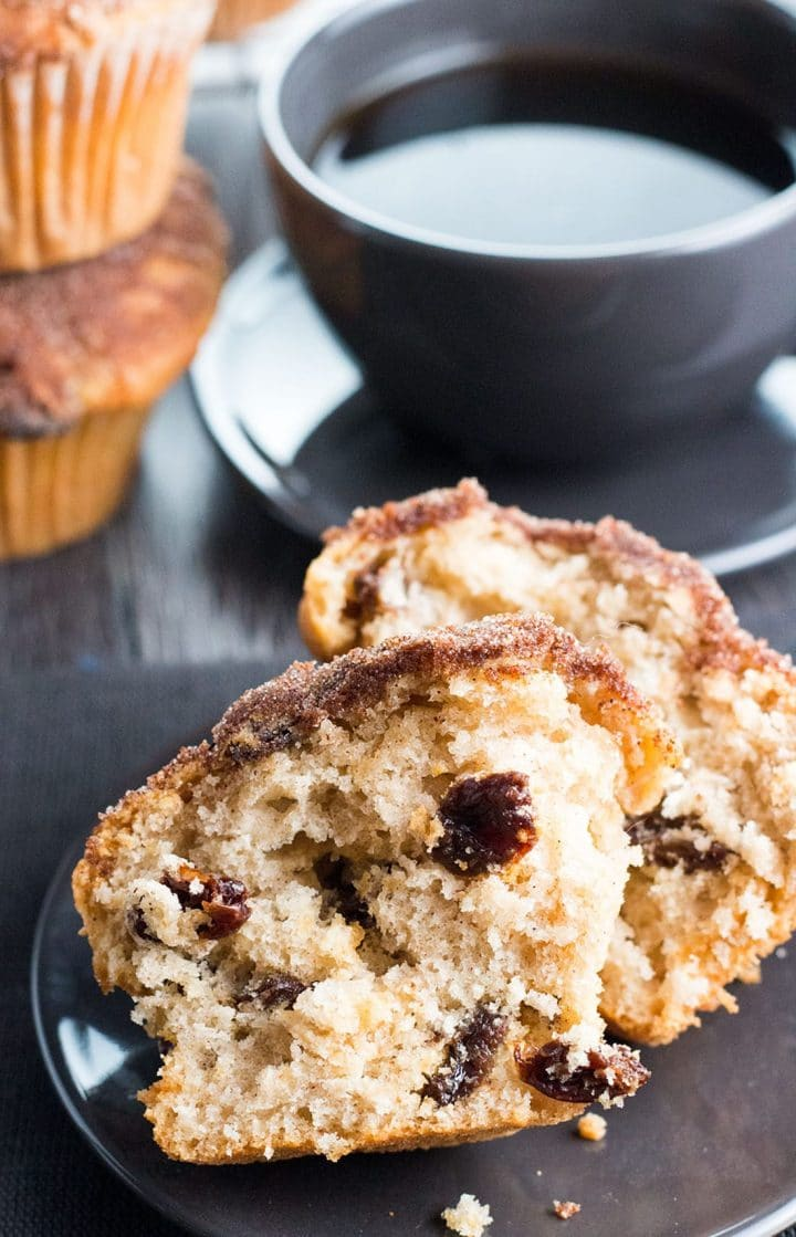 a Cinnamon Raisin Jumbo Muffin Topped with Cinnamon Sugar broken in half on a plate with a cup of coffee in the background