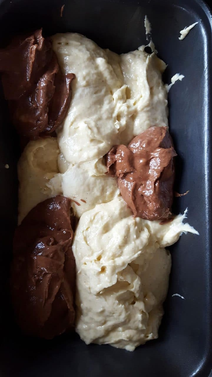 The batter in the spooned into the pan alternating between chocolate and vanilla