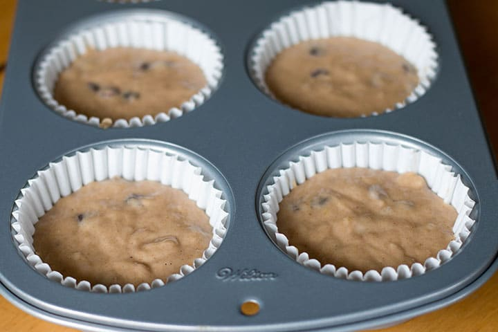 the batter added to the muffin papers in the pan