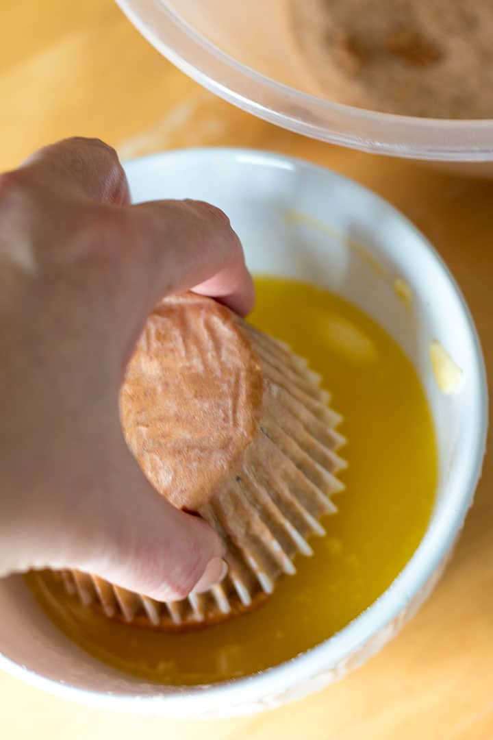 the muffin being dipped into the melted butter