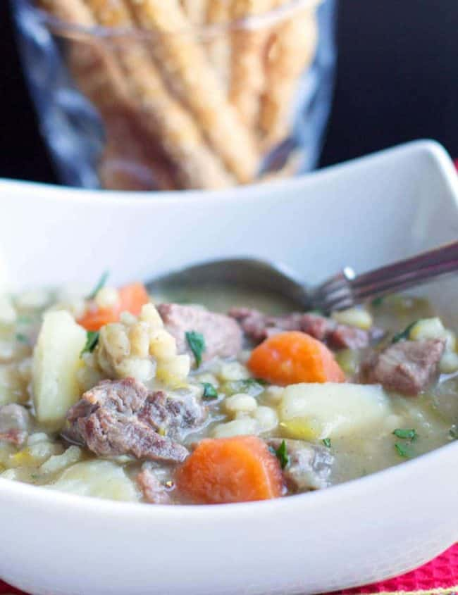 Classic Irish Stew in a bowl with a spoon and breadsticks