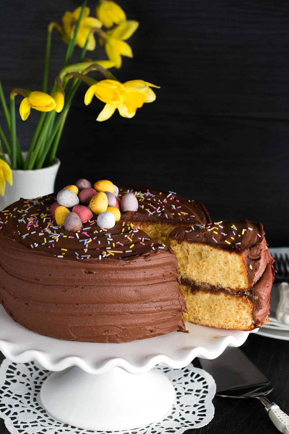 A piece of yellow celebration cake with chocolate frosting being removed from the whole cake, with spring flowers in the background