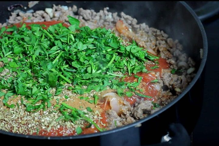 The fresh mint and parsley added to the pan with the beef and tomato mixture