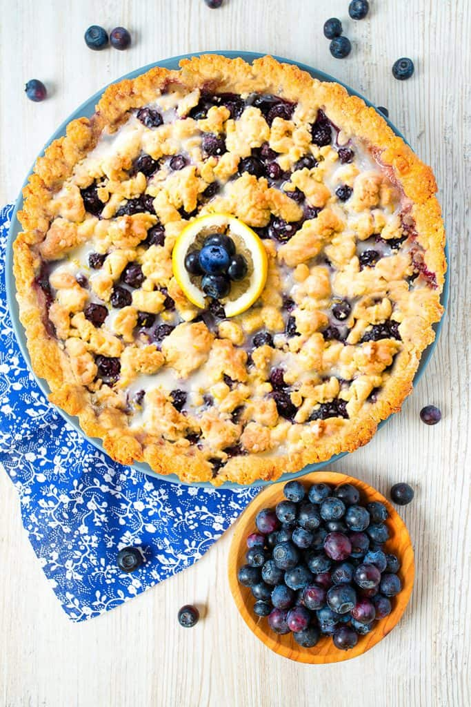 homemade blueberry tart on white wooden surface with a bowl of blueberries