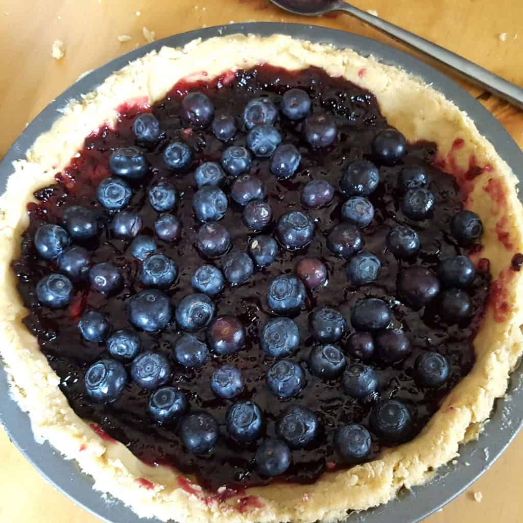 jam and blueberries in a pie shell