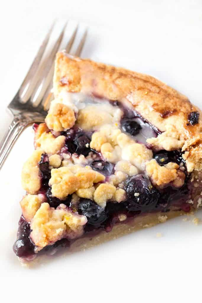 A slice of a blueberry tart with a white background